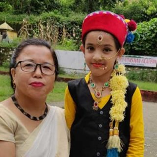 Principal with a student who participate fancy dress program
